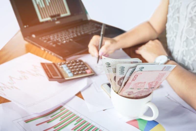 Mulher de negócios que conta o dinheiro e que analisa o relatório financeiro do gráfico com calculadora e caderno na mesa imagem de stock