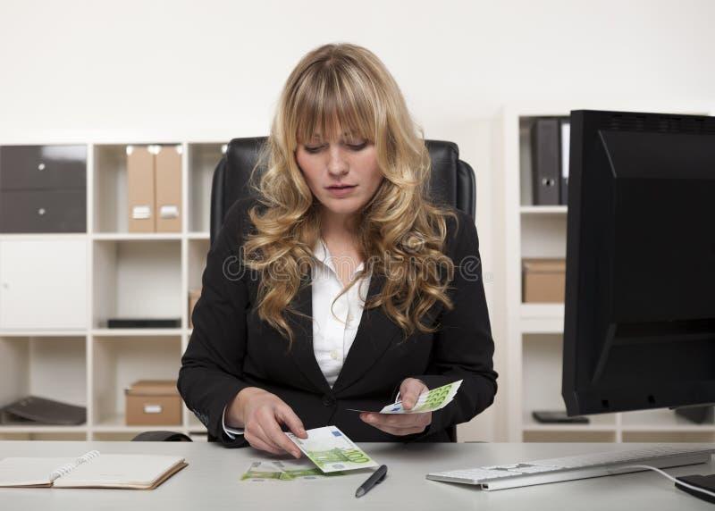 Mulher de negócios que conta para fora o dinheiro em sua mesa imagem de stock