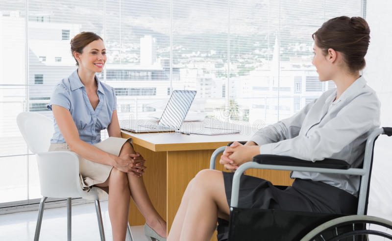 Mulher de negócios que conversa com colega deficiente fotografia de stock