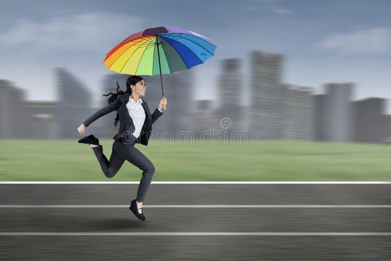 Mulher de negócios que corre com guarda-chuva colorido imagem de stock royalty free
