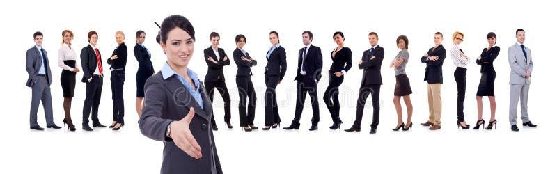 Mulher de negócios que dá boas-vindas a sua equipe do negócio imagem de stock