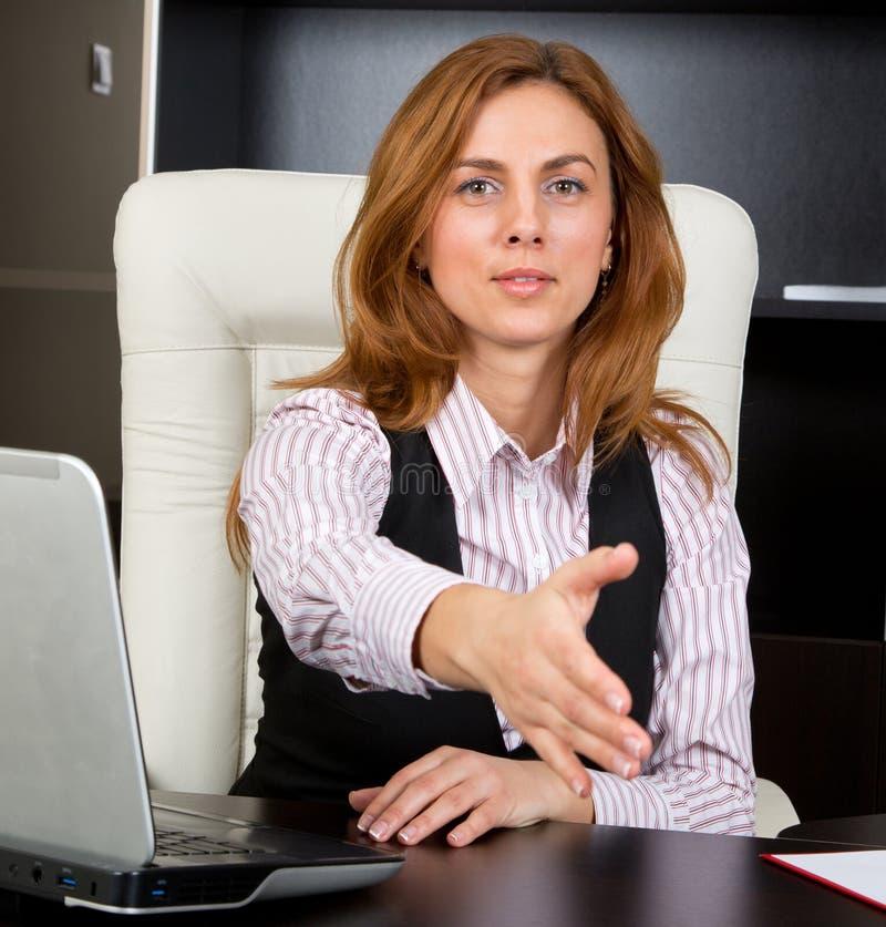 Mulher de negócios que dá o aperto de mão fotografia de stock