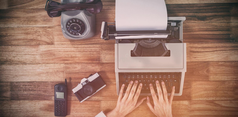 Mulher de negócios que datilografa na máquina de escrever pela câmera e pelo telefone do vintage foto de stock royalty free