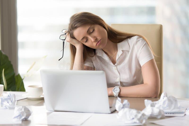 Mulher de negócios que dorme com cabeça disponível no trabalho fotografia de stock royalty free