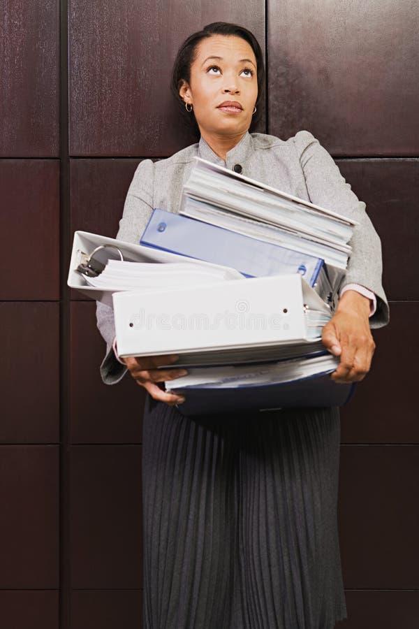 Mulher de negócios que esforça-se com os arquivos pesados fotografia de stock