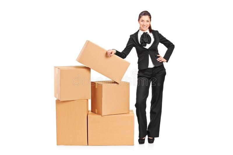 Mulher de negócios que está ao lado de uma pilha das caixas fotos de stock royalty free