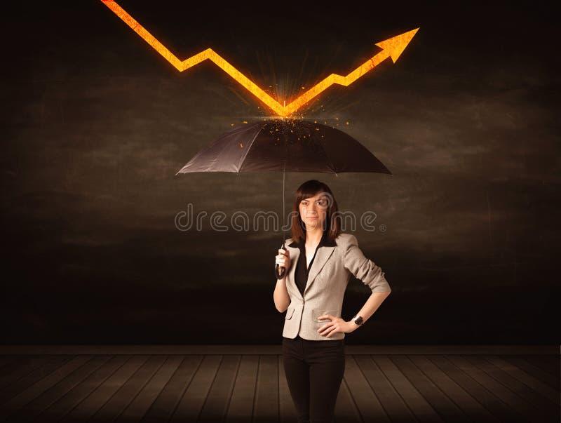 Mulher de negócios que está com o guarda-chuva que mantém a seta alaranjada imagens de stock royalty free