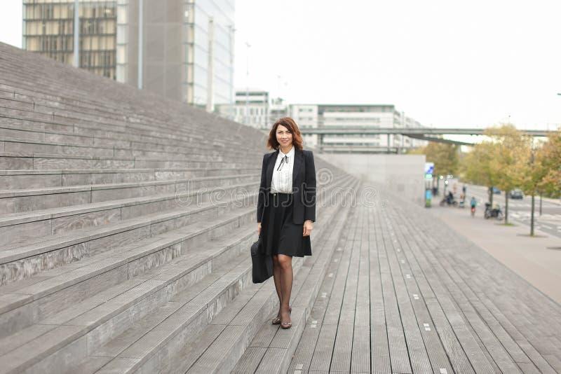 Mulher de negócios que está em escadas com saco e em construções altas no fundo imagem de stock royalty free