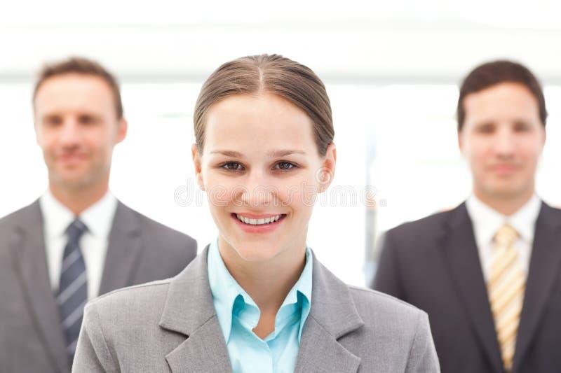 Mulher de negócios que está na frente de dois homens de negócios imagens de stock royalty free