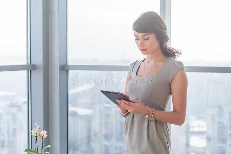 Mulher de negócios que está na sala da luz do sótão, datilografando, lendo o email, informação da consultação em linha, usando ap imagens de stock