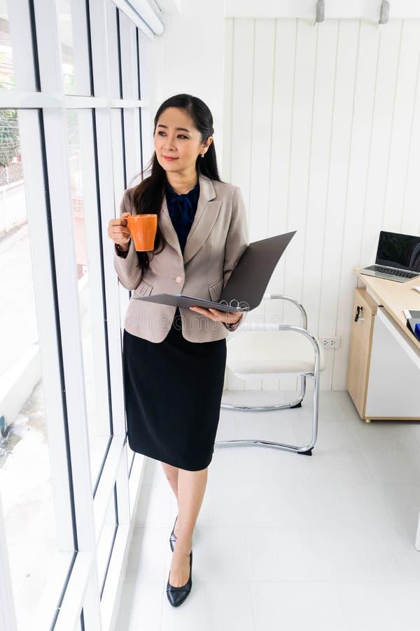 Mulher de negócios que está pela janela imagens de stock royalty free