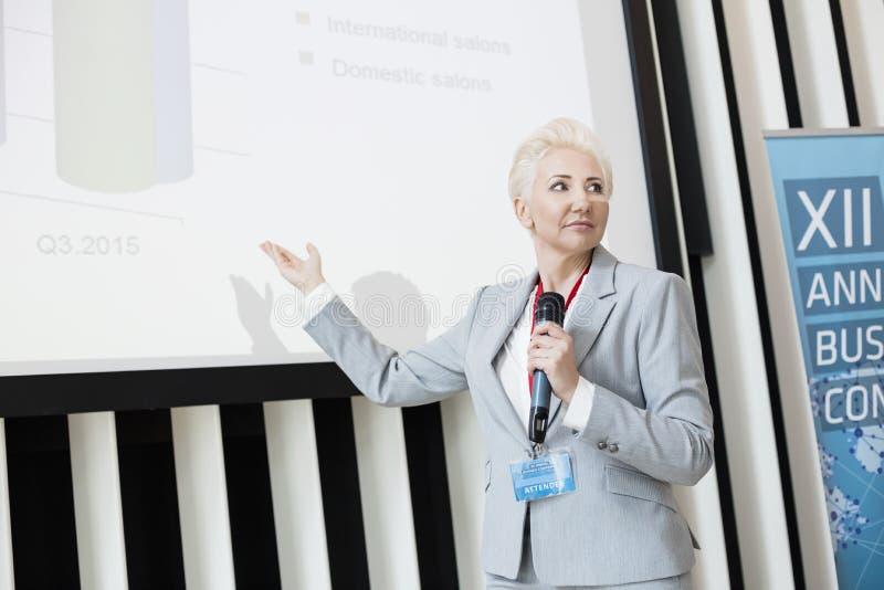 Mulher de negócios que explica a estratégia na tela de projeção no centro de convenções foto de stock