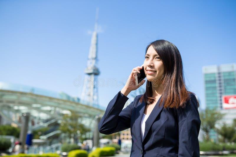 Mulher de negócios que fala ao telefone celular na cidade de Nagoya imagem de stock