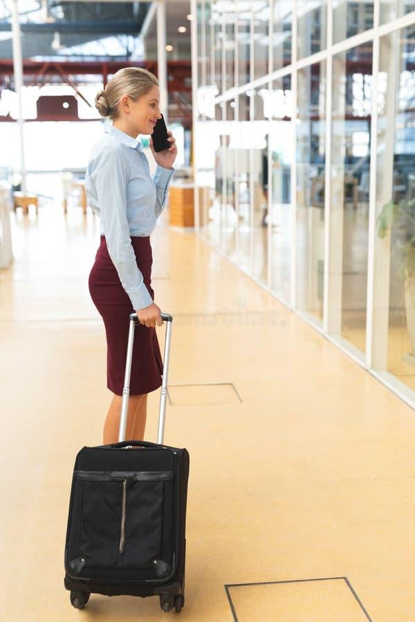 Mulher de negócios que fala no telefone celular ao estar com bagagem no corredor fotografia de stock royalty free