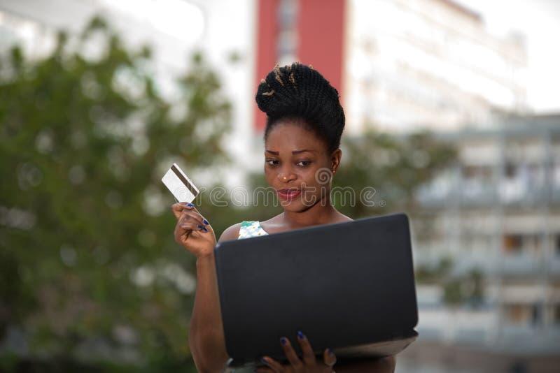 Mulher de negócios que faz a compra em linha através do portátil e do cartão de crédito foto de stock
