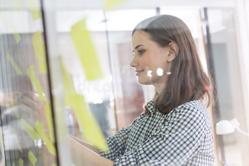 Mulher de negócios que faz estratégias em notas adesivas no escritório fotos de stock royalty free
