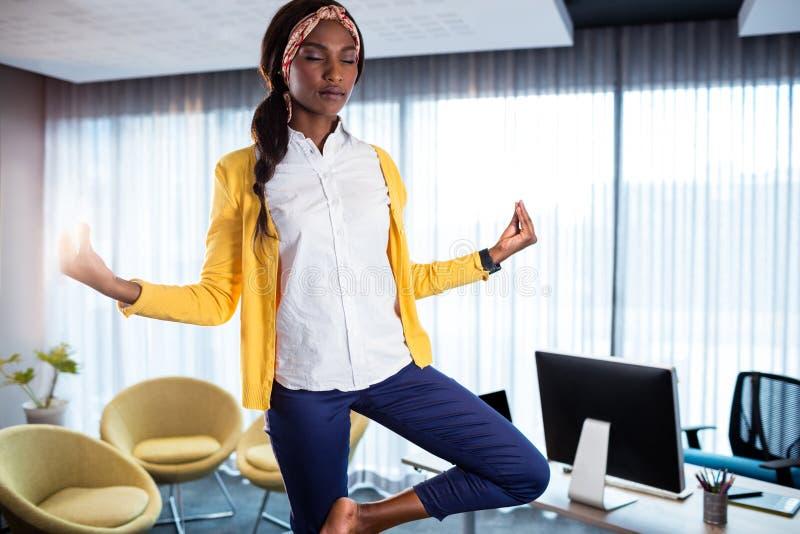 Mulher de negócios que faz a ioga imagem de stock
