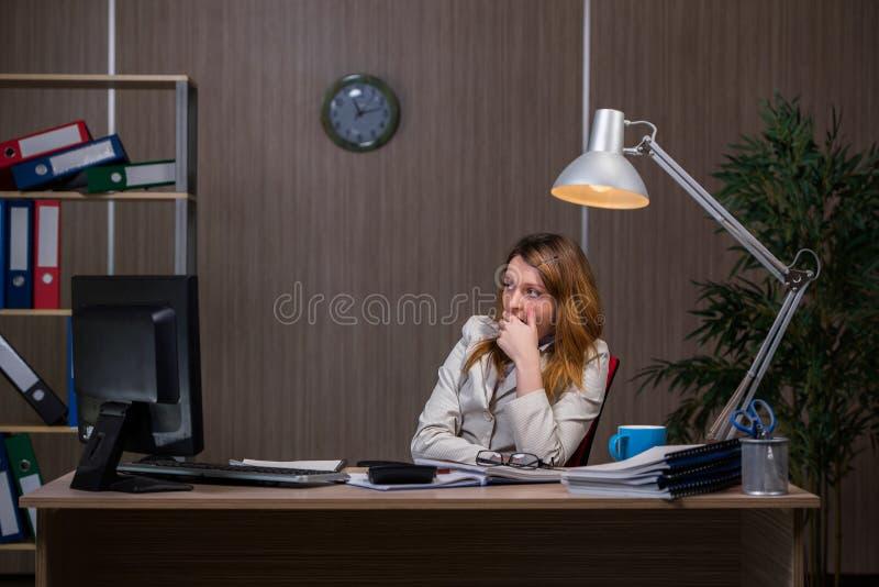 A mulher de negócios que fica no escritório para o muito tempo fotos de stock royalty free