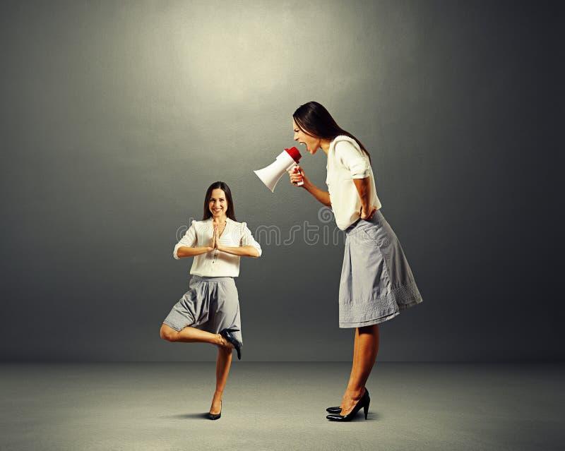 Mulher de negócios que grita na mulher pequena da ioga fotos de stock royalty free