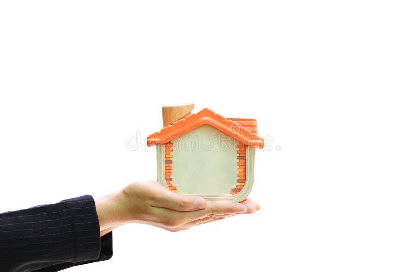 Mulher de negócios que guarda a casa de madeira no fundo branco, na casa nova e no conceito dos bens imobiliários fotografia de stock