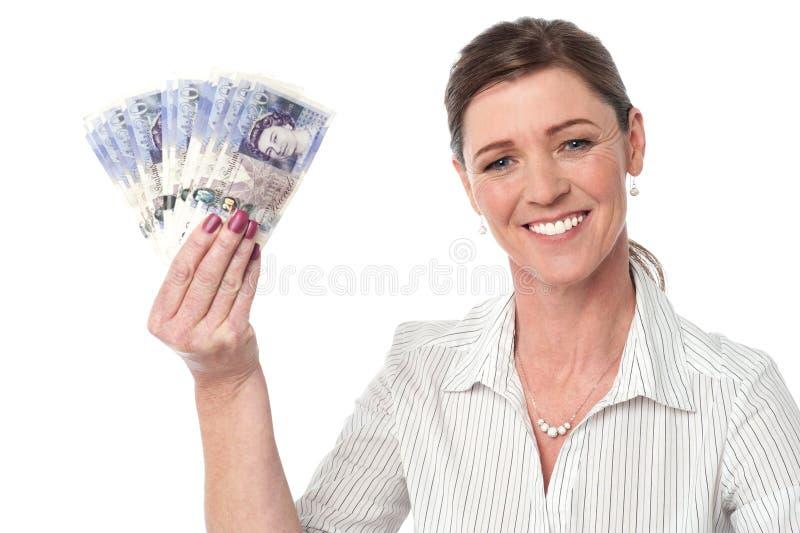 Mulher de negócios que guarda o fã de notas da moeda imagem de stock