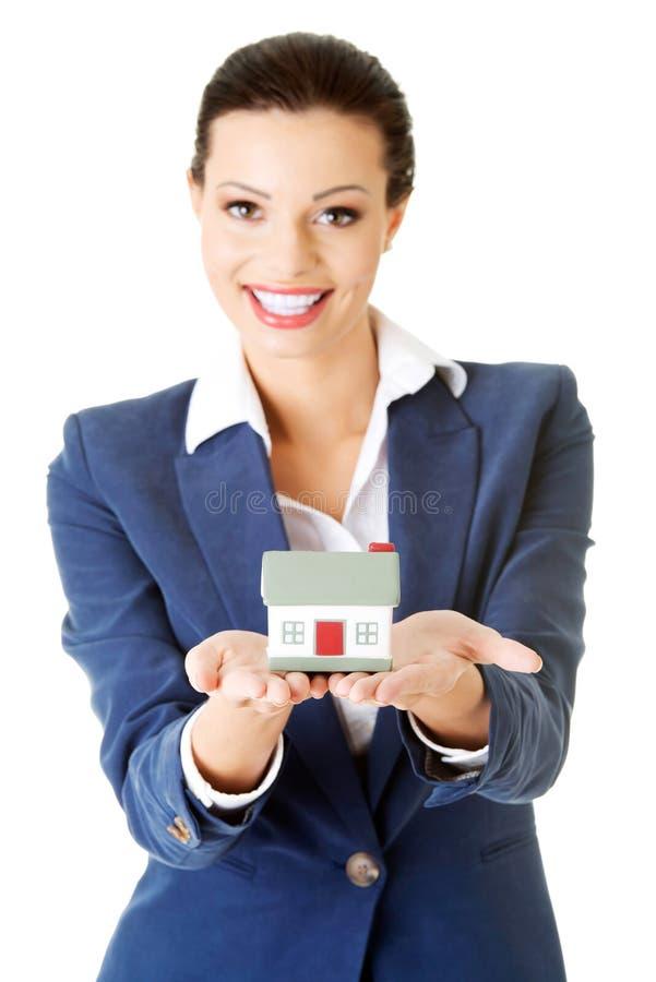 Mulher de negócios que guarda o modelo da casa - conceito do empréstimo de bens imobiliários imagens de stock royalty free