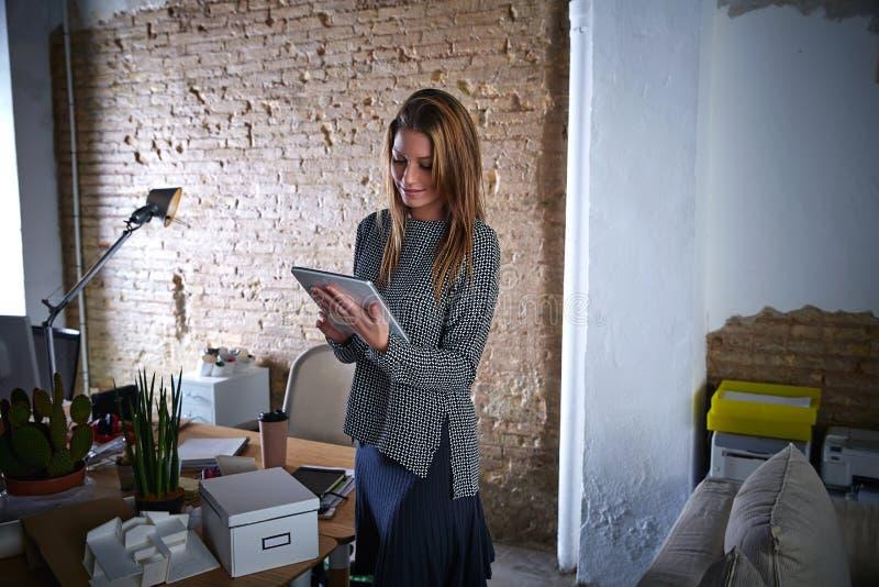Mulher de negócios que guarda o PC da tabuleta no escritório fotos de stock