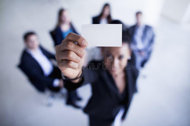 Mulher de negócios que guarda um cartão até a câmera Shannon Fagan Photography imagens de stock