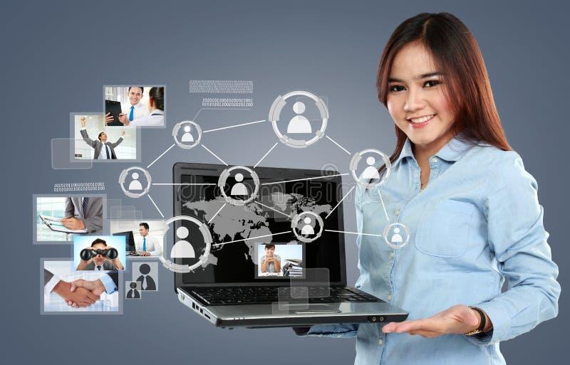 Mulher de negócios que guarda um PC do portátil e que surfa no netw social imagens de stock