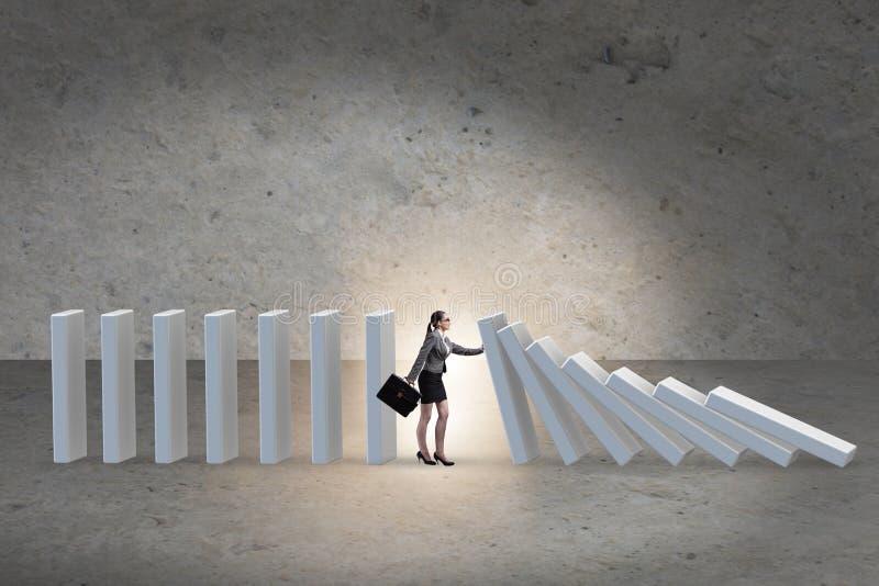 Mulher de negócios que impede o efeito de dominó no conceito do negócio fotos de stock
