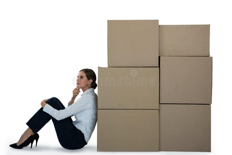 Mulher de negócios que inclina-se em caixas de cartão contra o fundo branco imagem de stock royalty free