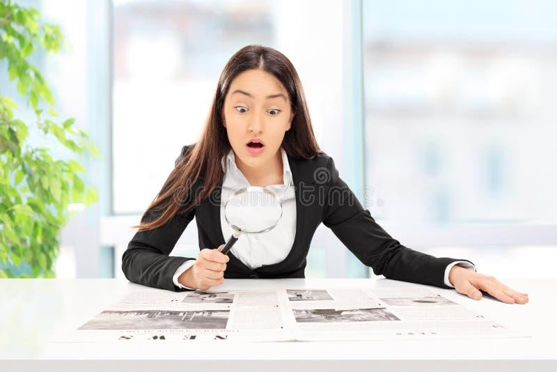 Mulher de negócios que lê a notícia com exame minucioso fotos de stock