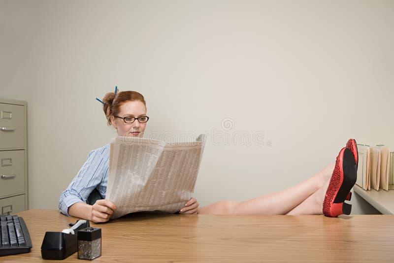 Mulher de negócios que lê um jornal fotos de stock royalty free