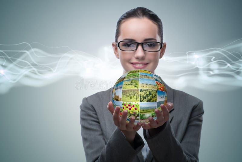 A mulher de negócios que mantém a bola feita de fotos da natureza fotos de stock