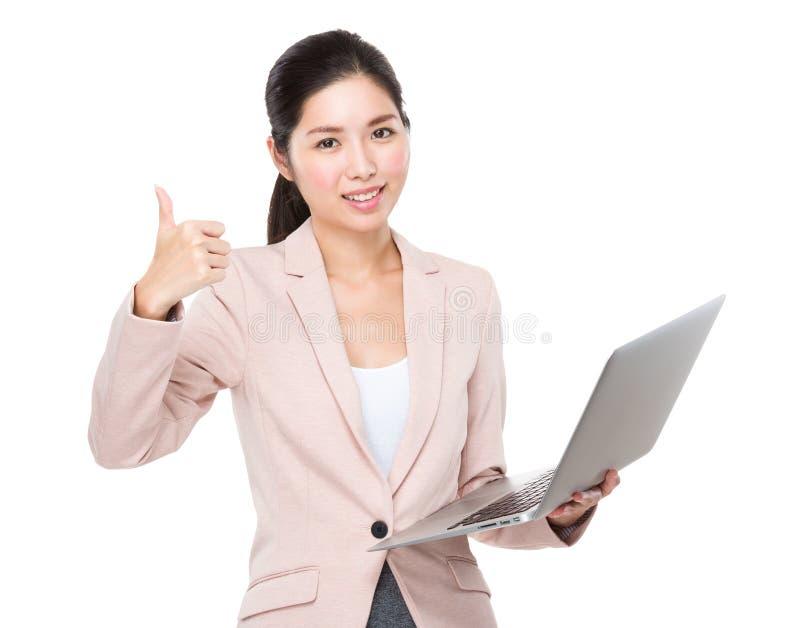 Mulher de negócios que mantém o laptop e o polegar fotos de stock