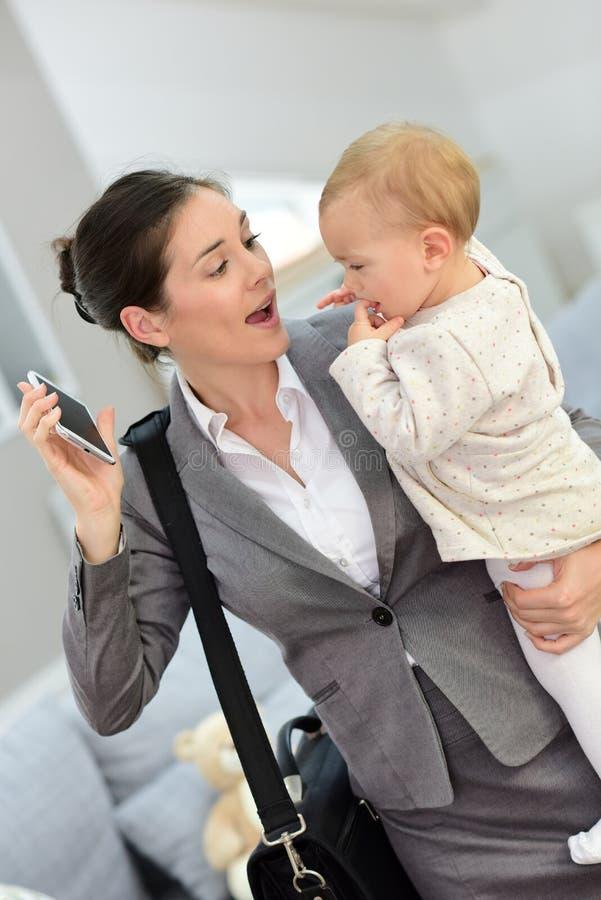 Mulher de negócios que mantém seus bebê e smartphone que estão atrasados para o trabalho imagens de stock royalty free