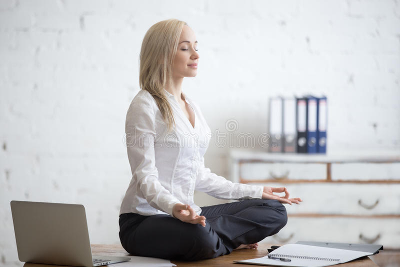 Mulher de negócios que medita em seu escritório imagens de stock