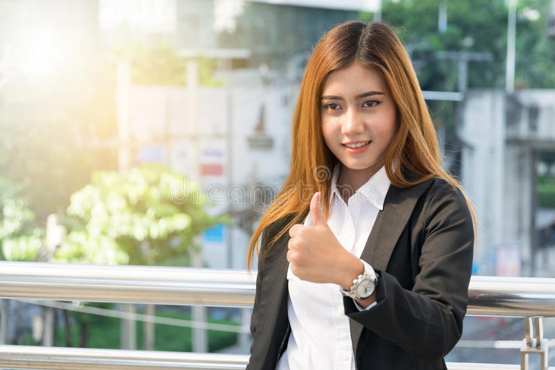 Mulher de negócios que mostra o polegar acima do gesto, fundo da cidade imagens de stock