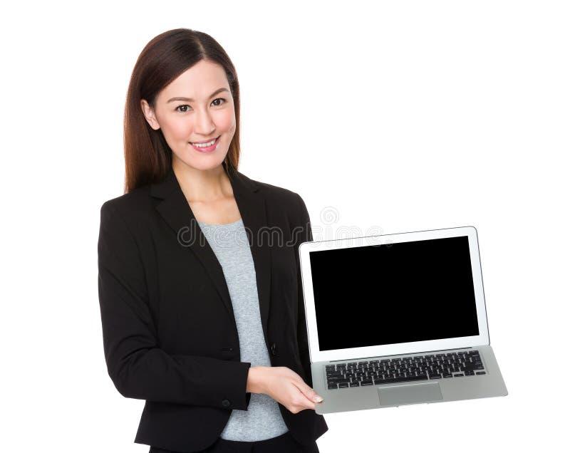 Mulher de negócios que mostra a tela vazia do laptop foto de stock royalty free