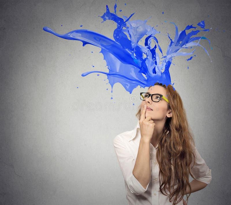 A mulher de negócios que olha acima com colorido espirra a saída de sua cabeça imagem de stock