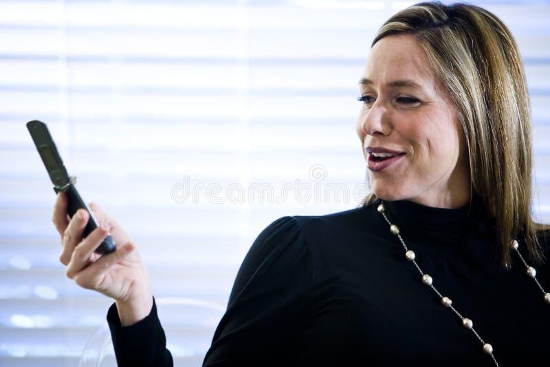 Mulher de negócios que olha o telefone móvel fotos de stock
