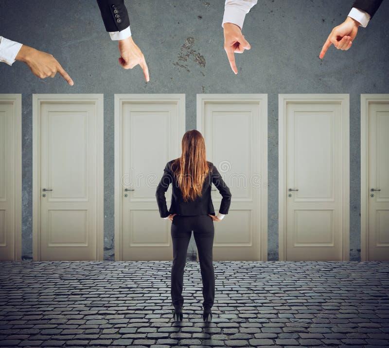 Mulher de negócios que olha para selecionar a porta direita Conceito da confusão e da competição imagem de stock royalty free