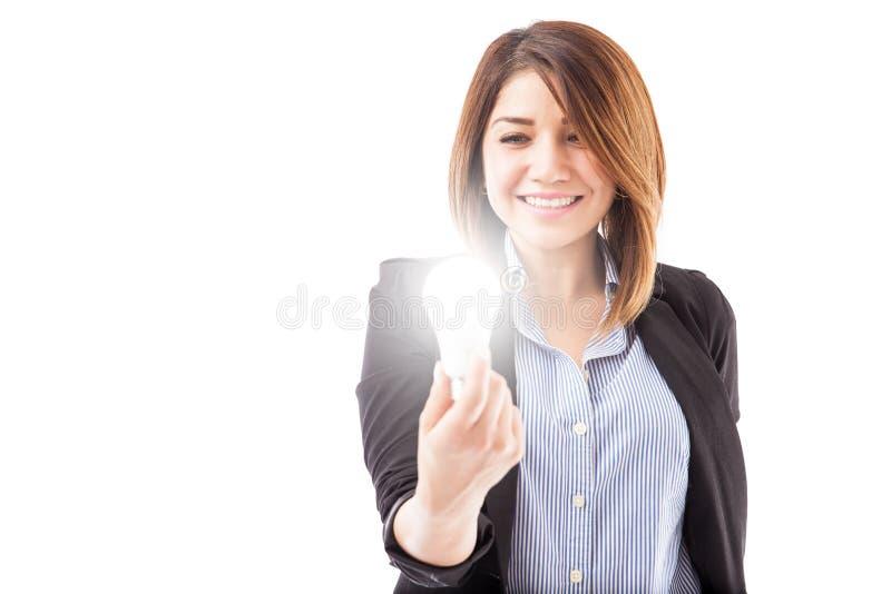 Mulher de negócios que olha uma ampola do diodo emissor de luz foto de stock