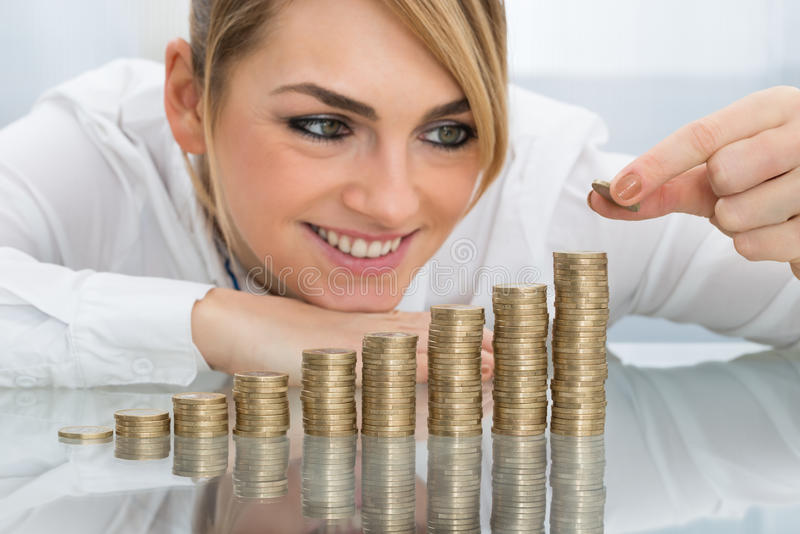 Mulher de negócios que põe a moeda sobre a pilha de moedas fotografia de stock