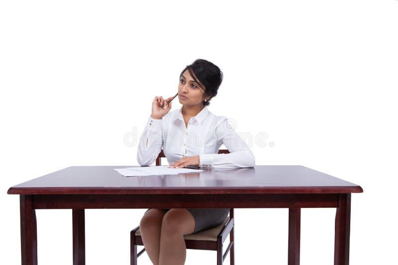 Mulher de negócios que pensa em sua mesa fotos de stock