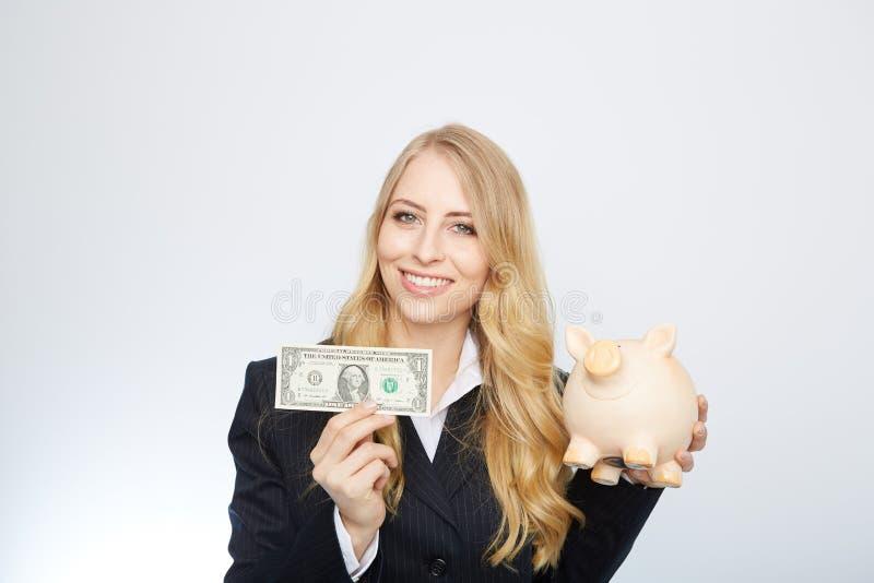 Mulher de negócios que prende o banco Piggy imagens de stock royalty free