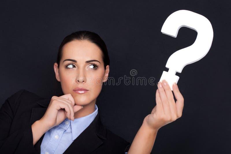 Mulher de negócios que prende um ponto de interrogação fotos de stock royalty free