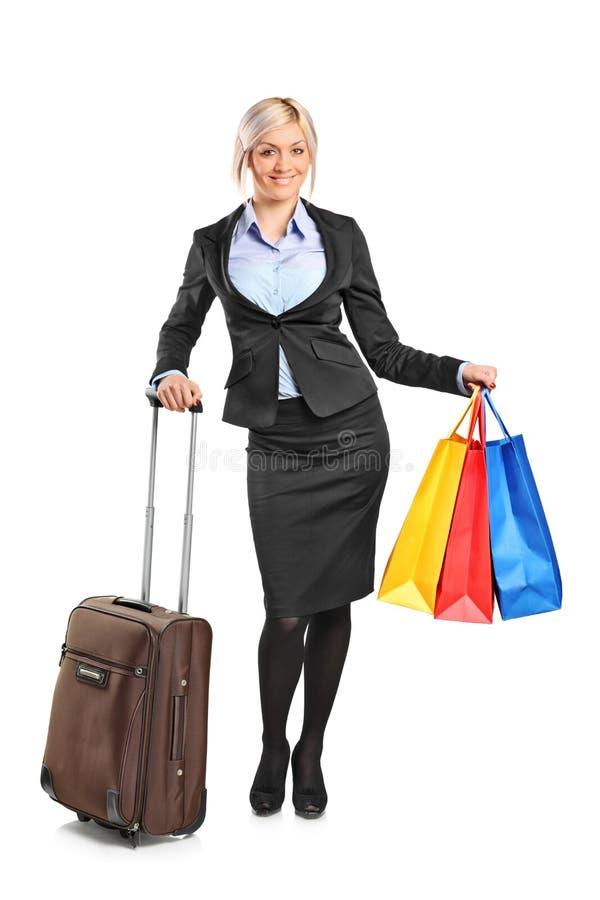 Mulher de negócios que prende uma mala de viagem e sacos de compra imagem de stock royalty free