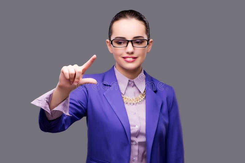 A mulher de negócios que pressiona o botão virtual no fundo cinzento fotografia de stock