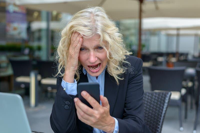 Mulher de negócios que reage no horror a seu móbil foto de stock royalty free